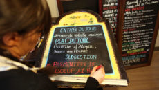 """TO GO WITH AFP STORY BY ISABELLE TOUSSAINT A woman writes on the menu board in a restaurant in Paris, on February 22, 2013, as she proposes a """"parmentier de boeuf"""" (shepherd's pie beef).   AFP PHOTO THOMAS SAMSON        (Photo credit should read THOMAS SAMSON/AFP/Getty Images)"""