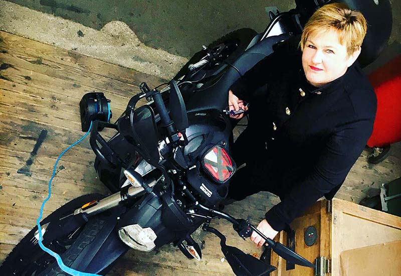 MYA MD Carla McKenzie charges her electric motorcycle through the consultancy's office window.